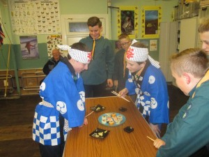 Scouts dressed in Japanese costume about to eat sushi.